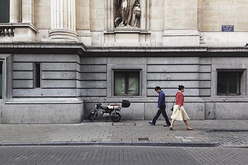 two people walking opposite direction street